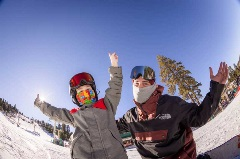 father and son with arms up wearing a face mask and snowboarding gear