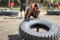 Athletic girl flipping a wheel at the Snow Summit Spartan Race
