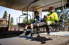 two mountain bikers sitting on a chairlift, giving a thumbs up