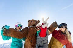 three female snowboarders with a wooden bear at Bear Mtn peak