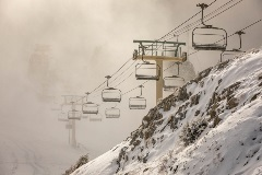 chairlifts near a snowy rock wall