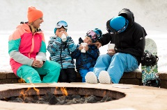 family of 4 sitting by a fireplace in their snow gear