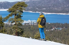 male skier looking down, lake in the background with snowy trees