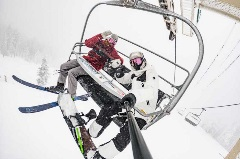 skiet and snowboarder on ski chairlift in snowy conditions