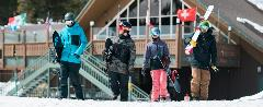 four friends carrying ski gear