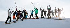 Group shot of skiers raising their poles in the air.