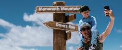 Father and son posing for a selfie at the Mammoth Sign.