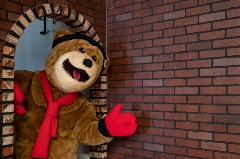 biggie the mascot hanging from a doorway, waving hi