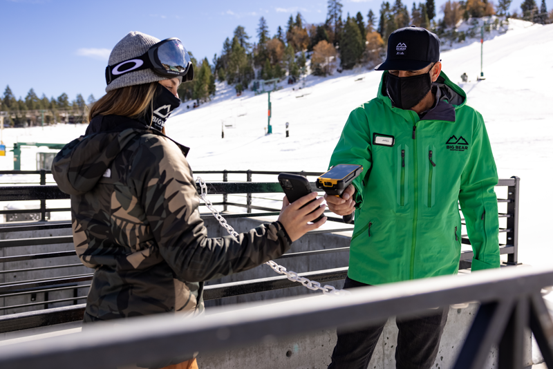 guest getting her lift ticket scanned by bbmr employee