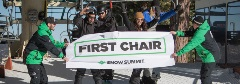 riders breaking through a first chair banner at snow summit's opening day
