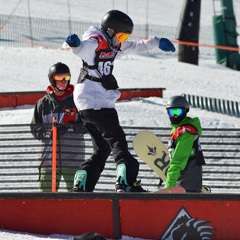 kid doing a trick on the rail at bear mountain during the USASA race