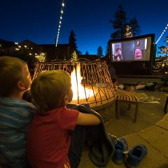 two kids watching a movie on a blow up screen outside of Snow Summit base area