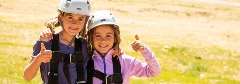two girls giving a thumbs up after ziplining