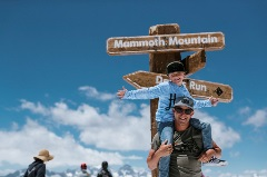 kid on dad's shoulders in front of mammoth sign