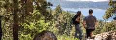 bobsled hiking trail at snow summit, two people looking at big bear lake from the top