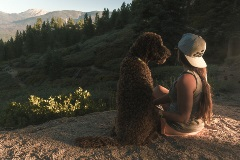 girl wearing a snow summit hat sitting with her dog on a hiking trail