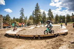 kids on mountain bikes riding a pump track
