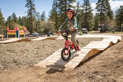 kid on mountain bikes riding a pump track