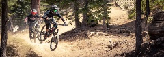 two mountain bikers going downhill on a trail