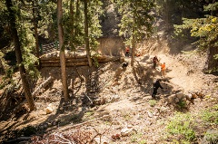 5 members of trail crew working on a dirt mtb trail