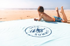 kid laying on a blanket on the beach