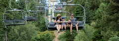 family of 4 riding the scenic sky chair through the trees