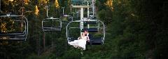 bride and groom on a chairlift kissing
