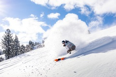 skier riding in the snow on a bluebird day