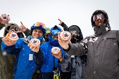 people holding up bear mountain branded donuts