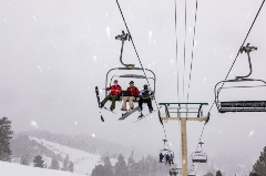 three riders on a chairlift with snow falling