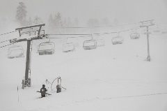 snow patrol standing in snow with chairlifts