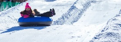 girl with pink beanie riding down a hill in a snow tube
