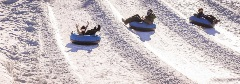 two people riding an inner tube down a snowy hill