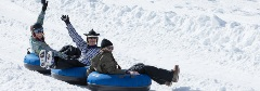 3 people riding in an inner snow tube on the snow
