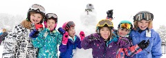 group of girls in snow gear with a snowman