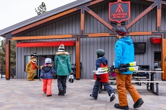 family of skiers and snowboarders walking into the adventure academy