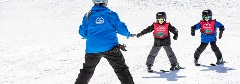 two kids taking a ski lesson with an intructor