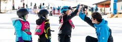 kids taking a ski lessons, kid giving his instructor a high five