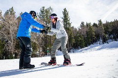 girl taking a lessons with an instructor for snowboarding