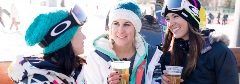 3 girls in snowboard gear, holding a beer