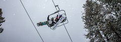 three guys on a chairlift while it is snowing