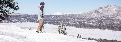 snowboarder over looking a snow covered lake
