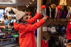 girl in red snow coat shopping beanies