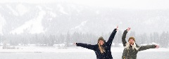 two girls near a snowy lake throwing their hands up