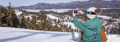 girl taking a picture with a snowy lake view