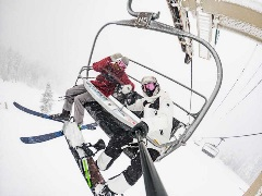 skier and snowboarder on chairlift taking a selfie