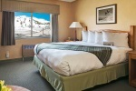 Queen bed in hotel room with snowy mountain view